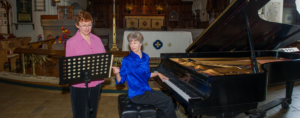 Members Beth Harmon and Judy Coleman rehearse for a performance.